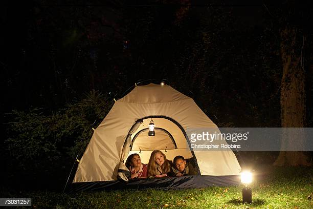 Three girls (10-11, 12-13) lying in tent in garden at night