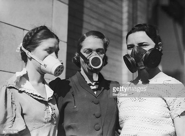 Three girls modelling various dustbowl masks to be worn in areas where the amount of dust in the air causes breathing difficulties circa 1935
