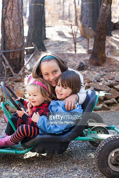 three girls (12-23 months, 2-3, 8-9) on go-cart - 12 23 months stock pictures, royalty-free photos & images