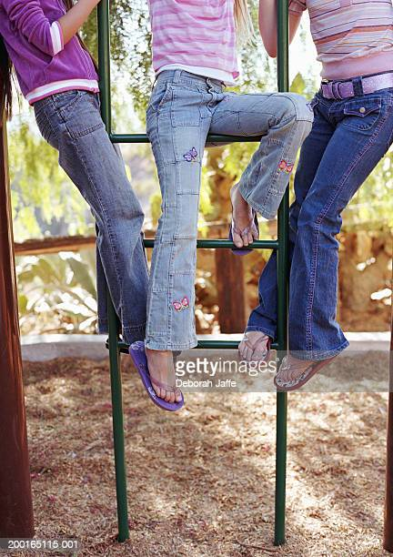 three girls (8-10) on jungle gym, low section - girl wear jeans and flip flops stock photos and pictures