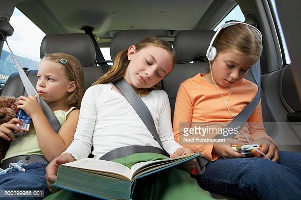 three girls (6-8 years) on rear car seat, close-up - family inside car stock photos and pictures