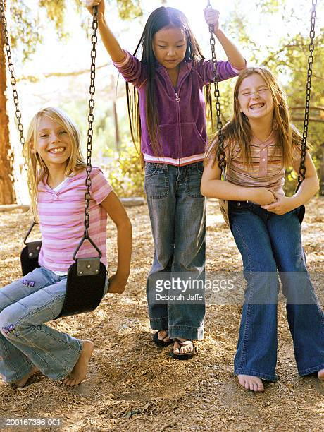 three girls (8-10), one standing between others on swings - girls barefoot in jeans stock photos and pictures