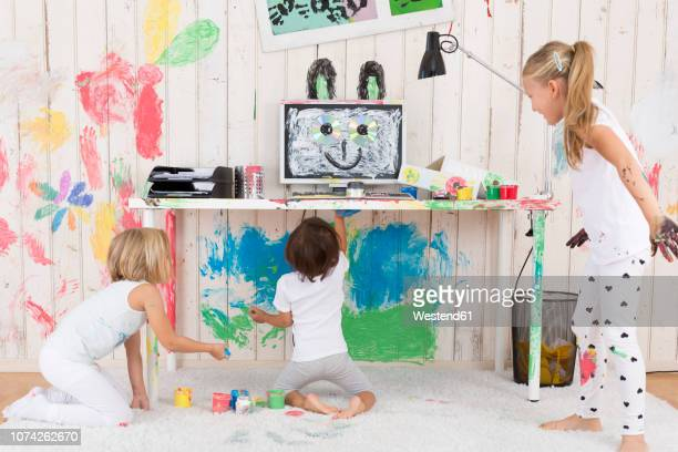 three girls painting office with finger paint - chaos stock-fotos und bilder