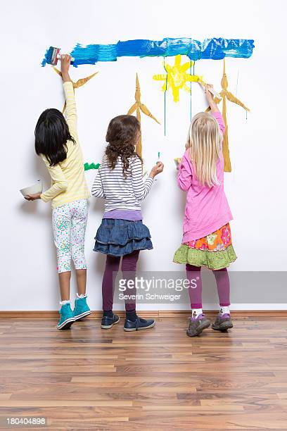 three girls painting wind turbines on wall - malen stock-fotos und bilder