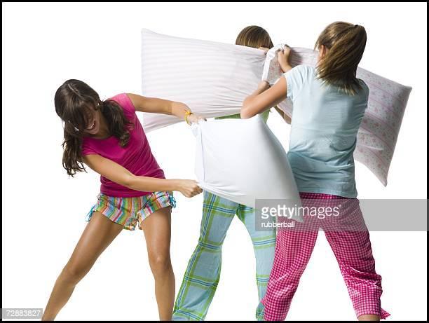 Three girls pillow fighting