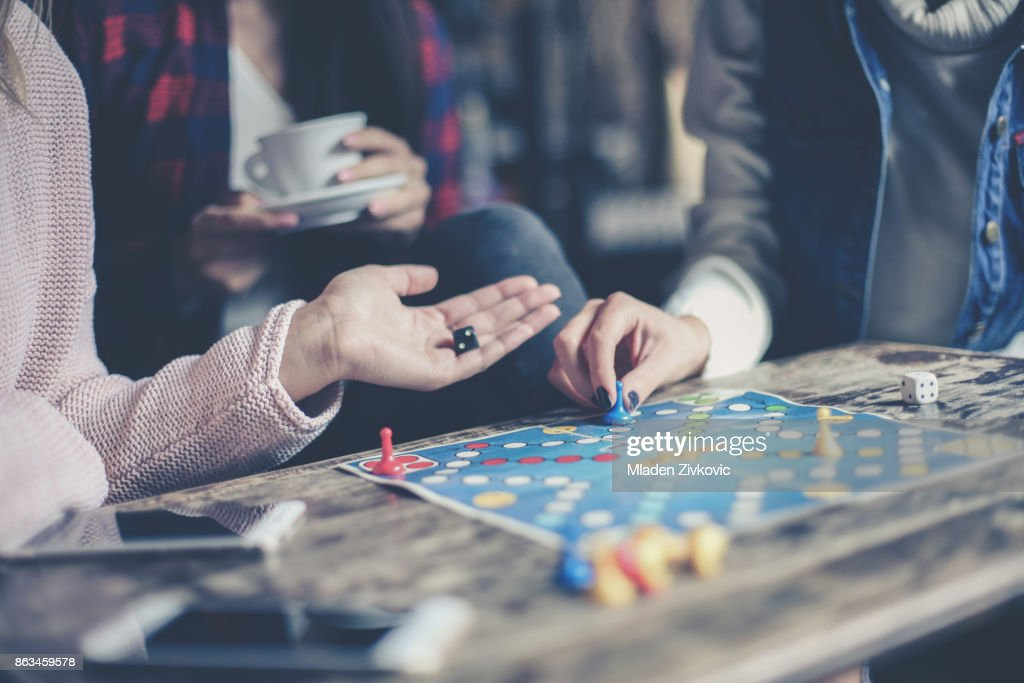 Three girls play together a social game. Focus on hand. : Stock Photo