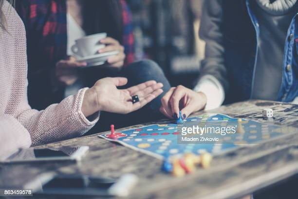 three girls play together a social game. focus on hand. - game board stock photos and pictures