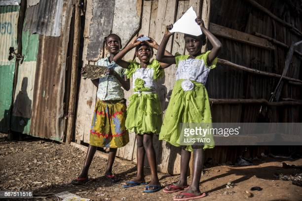 Three girls play with the reflection of mirrors on October 28, 2017 in the Mathare slums of Nairobi, a stronghold of Kenyan opposition leader. -...