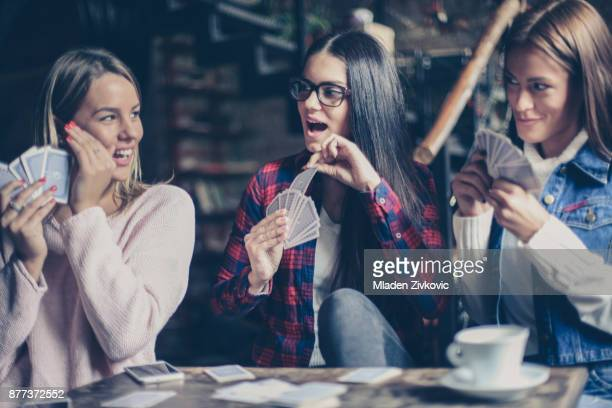three girls playing card in cafe. - poker card game stock photos and pictures