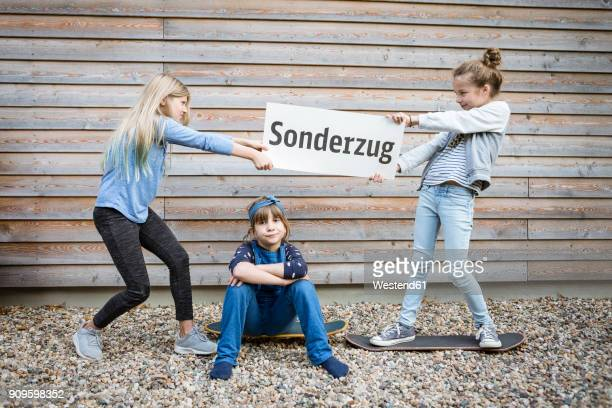 Three girls playing in front of a wooden facade
