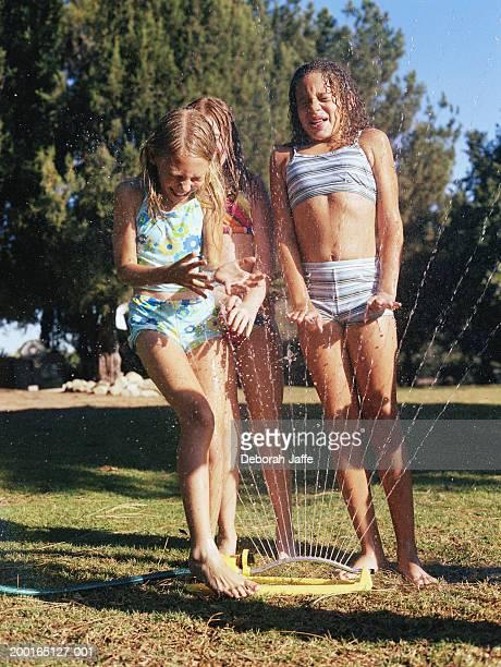 three girls (8-10) playing in sprinklers - 10 11 jahre stock-fotos und bilder