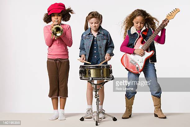 Three girls (8-9) playing instruments together, studio shot