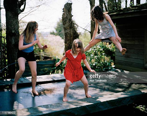 three girls playing on a trampoline - newpremiumuk stock pictures, royalty-free photos & images