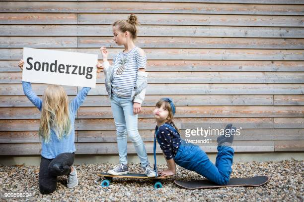 Three girls playing together in front of a wooden facade