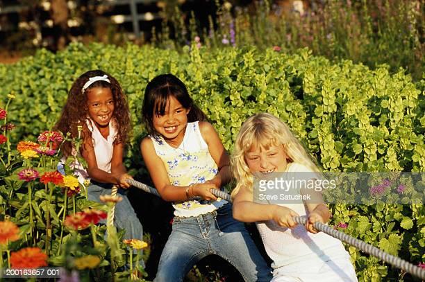 Three girls playing tug of war in garden