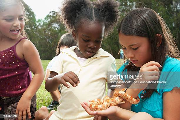 three girls playing with a small snake
