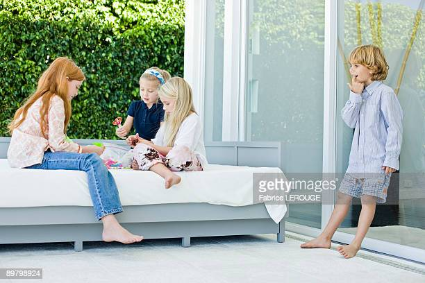 Three girls playing with toys and a boy looking at them