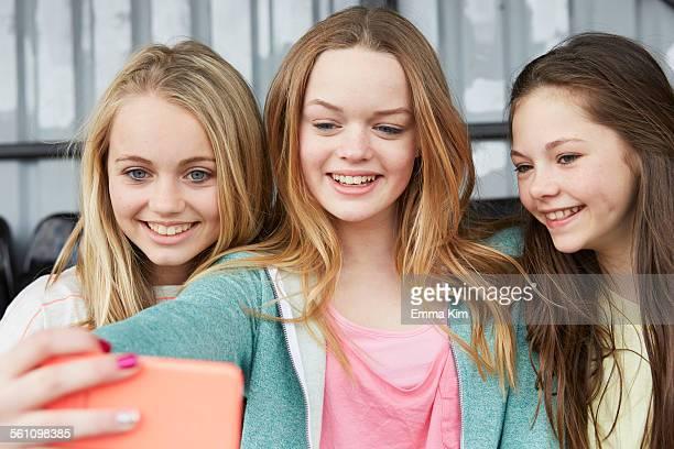 Three girls posing for smartphone selfie in shelter