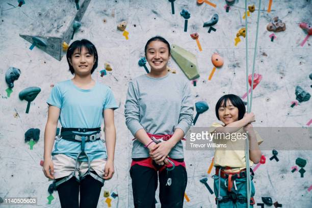 three girls preparing to practice at a rock climbing gym - 10歳から11歳 ストックフォトと画像