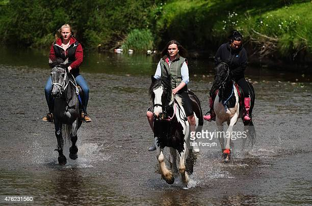 Three girls ride their horses through the River Eden during the Appleby Horse Fair on June 7 2015 in Appleby England The fair is an annual gathering...
