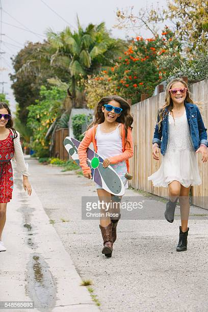 Three girls running down street, one with skateboard