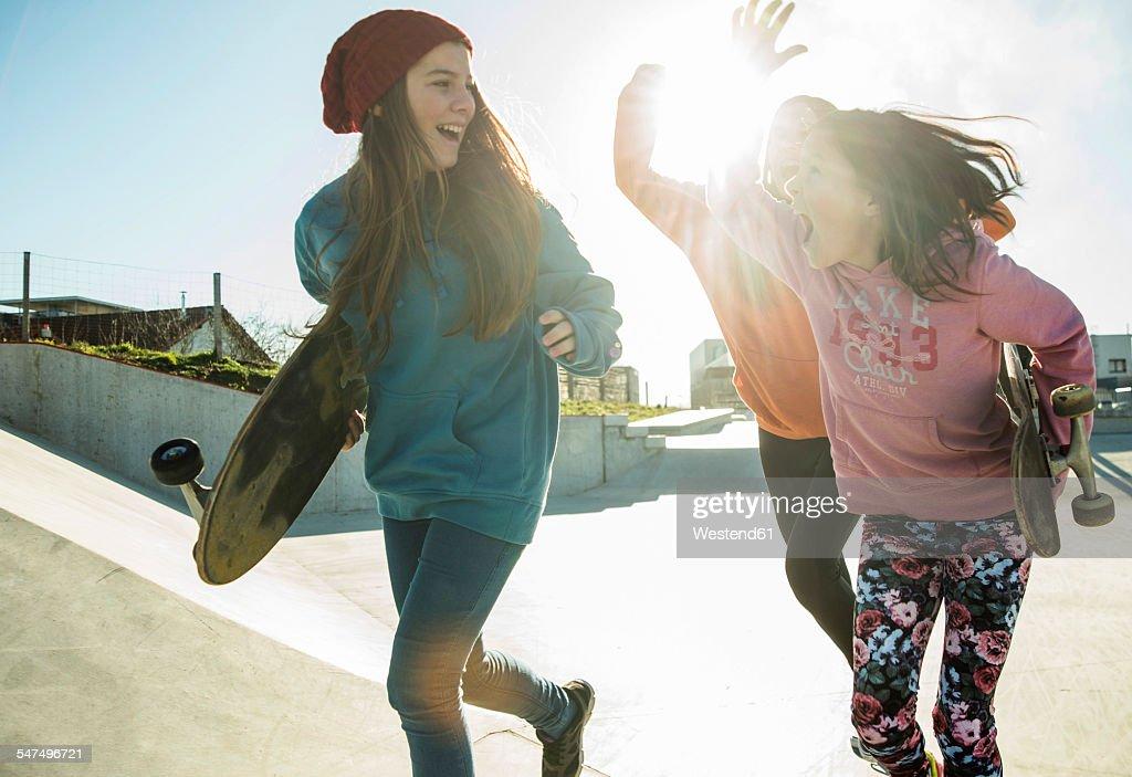 Three girls running in skatepark : Stock-Foto