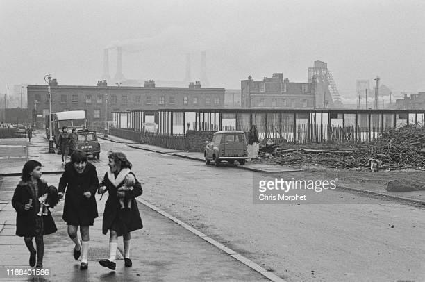 Three girls sharing a joke on a street near Belmore Place in Nine Elms London 28th December 1966 In the background is Battersea Power Station