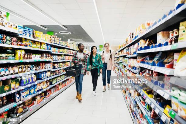 three girls shopping in super market - aisle stock pictures, royalty-free photos & images