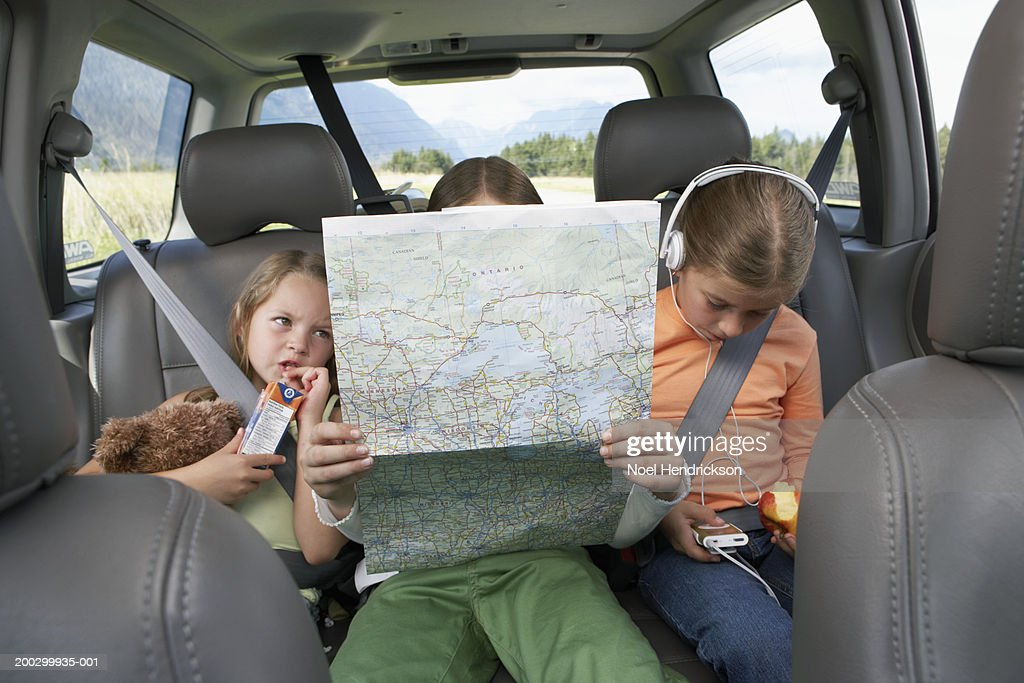 Three girls (6-8 years) sitting on rear seat of car on road trip : Stock Photo