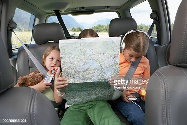 three girls (6-8 years) sitting on rear seat of car on road trip - family inside car stock photos and pictures