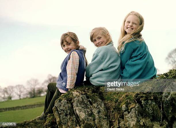 three girls (6-8) sitting on rock looking over shoulder, portrait - only girls stock pictures, royalty-free photos & images