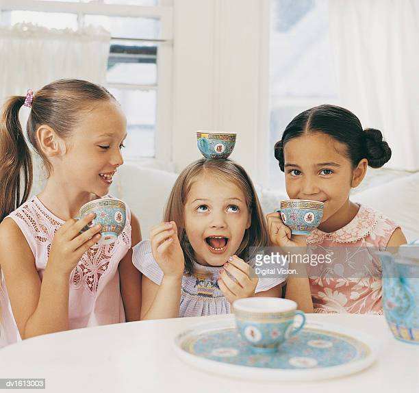 Three Girls Sitting Side by Side Having a Tea Party And Making Fun
