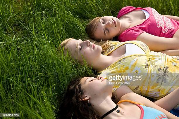 Three girls sleeping in the grass
