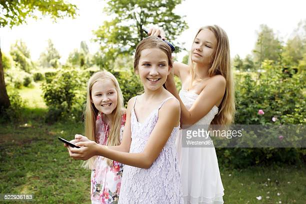 Three girls spending their time with hairdressing