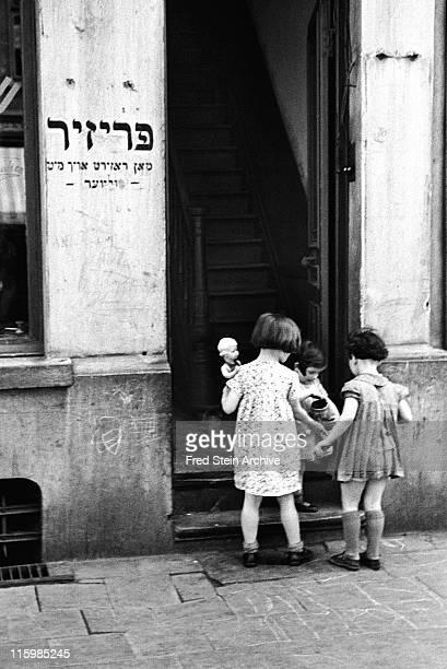 Three girls stand in an open doorway of a building in the Jewish quarter Antwerp Belgium 1937