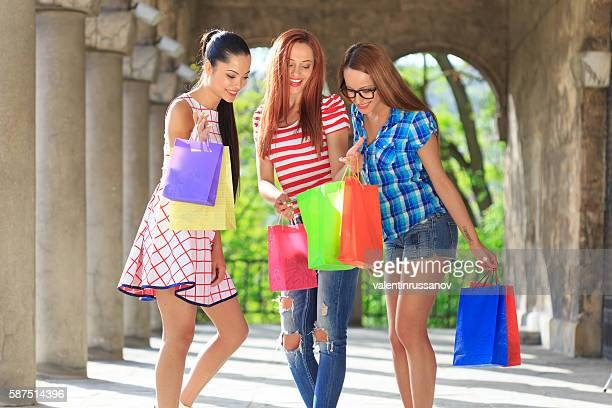 Three girls standing and looking at their new purchases