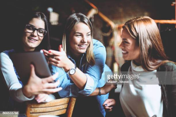 Three girls students in cafe using digital tablet and having conversation.