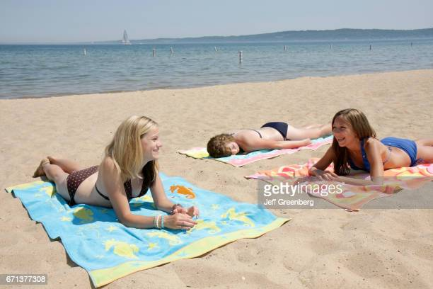 Three girls sunbathing on the beach at Clinch Park