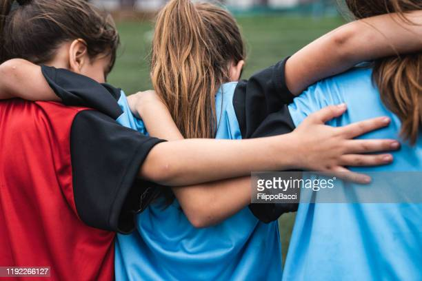 three girls supporting each other while playing soccer - sports team stock pictures, royalty-free photos & images