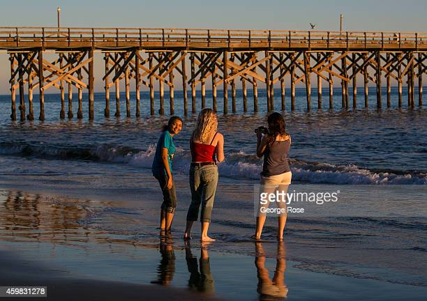 Three girls take pictures near Gaviota State Beach pier at sunset on November 26 in Santa Barbara California Because of its close proximity to...