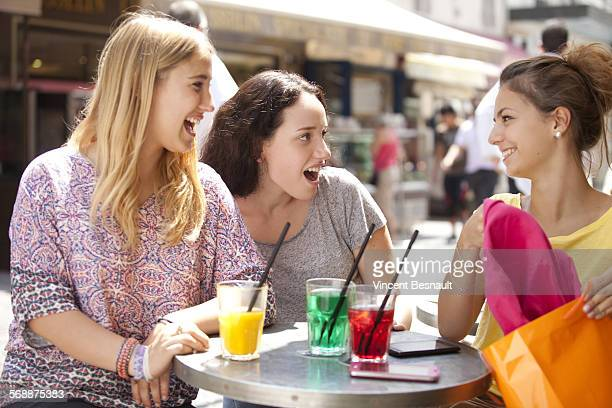 Three girls talking shopping a a cafe