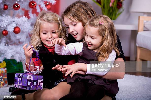 Three girls unpacking Christmas gifts