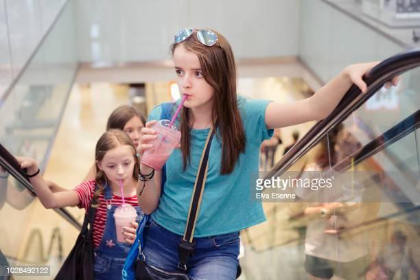three girls using an escalator in a shopping mall, whilst drinking smoothies - mädchen 14 jahre stock-fotos und bilder