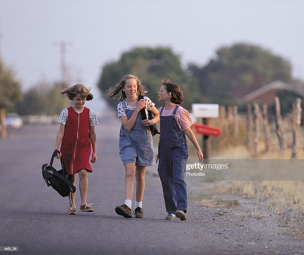 three girls walk home from school on a country road surrounded by trees and fence posts : Stockfoto
