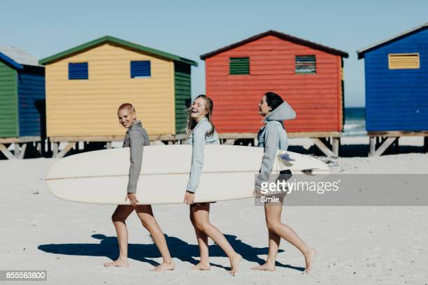 Three girls walking with a long board