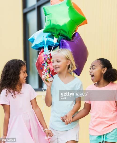 Three girls walking with balloons