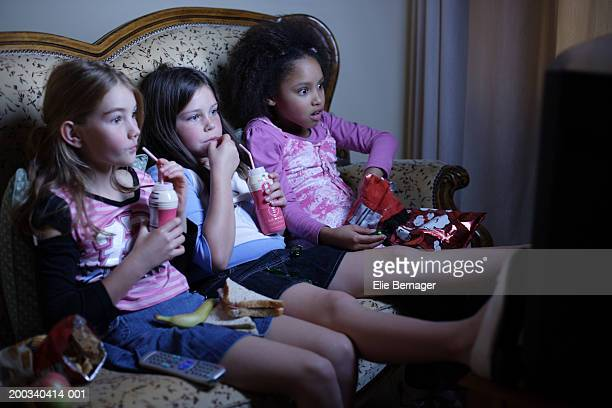 Three girls (7-9) watching televsion, shocked expressions on faces