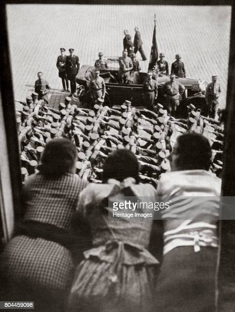 Three girls watching the traditional parade of SA stormtroopers Nuremberg Germany c19231938 Adolf Hitler stands in the car reviewing the parade...
