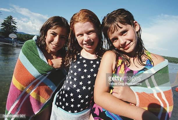 Three girls (10-12) wearing beach towels outdoors, smiling, portrait
