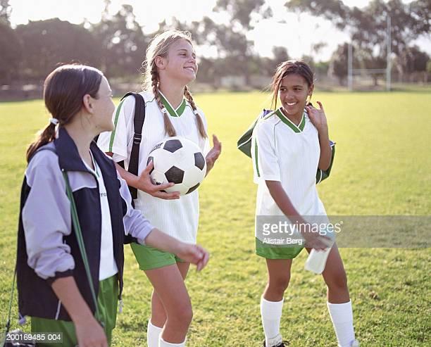 Three girls (11-13) wearing football kit walking in field, smiling